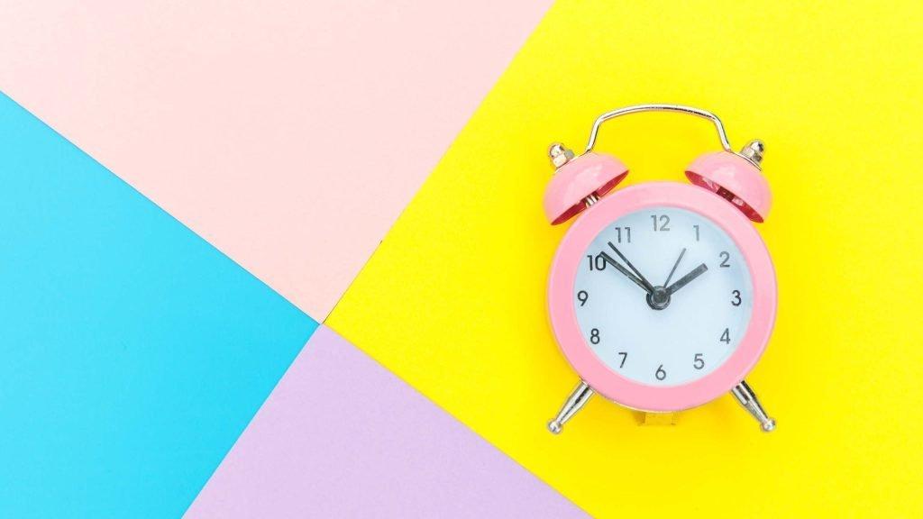 Cómo se dice la hora en inglés reloj rosa sobre fondo de colores